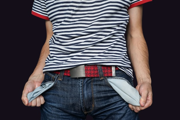 Povero uomo in jeans con tasca vuota isolata sul nero