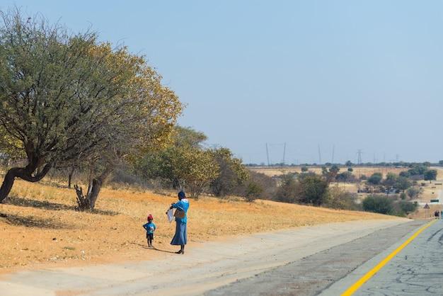 Povera gente che cammina sul ciglio della strada in namibia, africa.