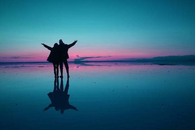 La pop art in stile blu e rosa silhouette colorata di coppia felice che apre i bracci sulla superficie di allagamento delle saline di uyuni al crepuscolo, bolivia, sud america
