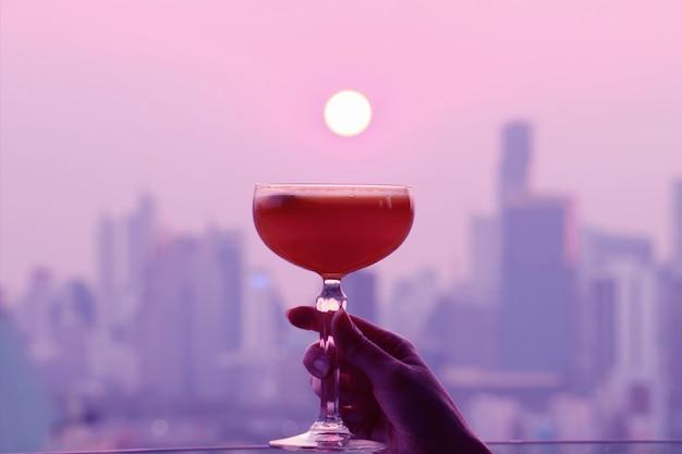 Bicchiere da cocktail colorato rosa e viola in stile pop art in mano con il sole che tramonta sulla città
