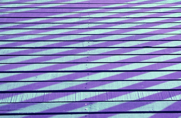 Ombra e luce colorata in stile pop art viola e blu della ringhiera che si riflette sulla passerella di legno