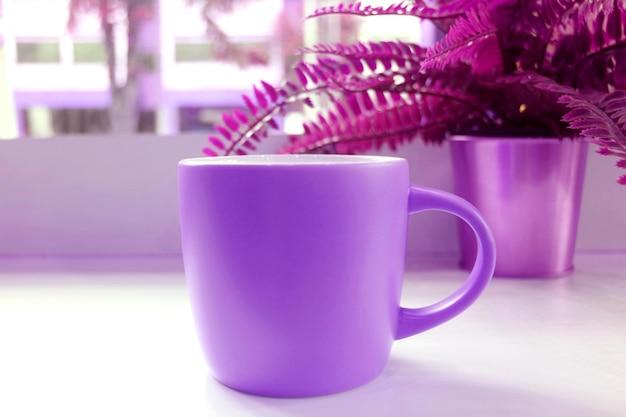 Tazza da caffè di colore viola vivido in stile pop art con felci in vaso su un tavolo