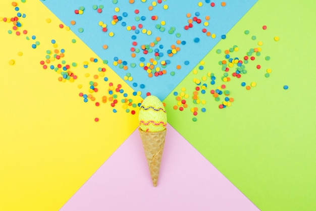Colori pop. priorità bassa multicolore festiva con granelli di zucchero luminosi sparsi su carta, uovo di pasqua dell'estremità del cono di wafer.