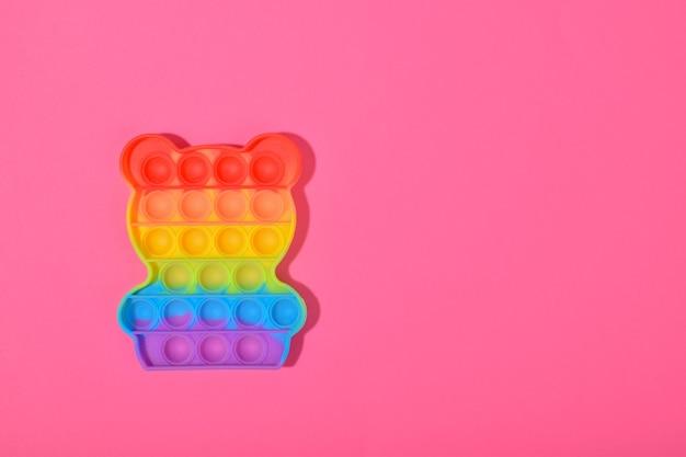 Pop it giocattolo in silicone su sfondo rosa.