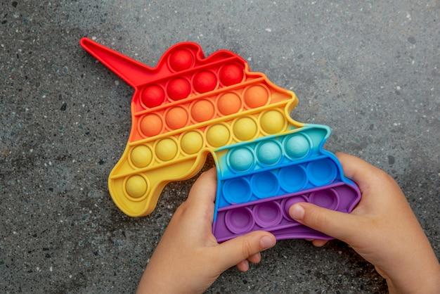 Giocattolo pop it, colori dell'arcobaleno, a forma di unicorno. il giocattolo antistress colorato, multicolore e sensoriale si agita nelle mani dei bambini.