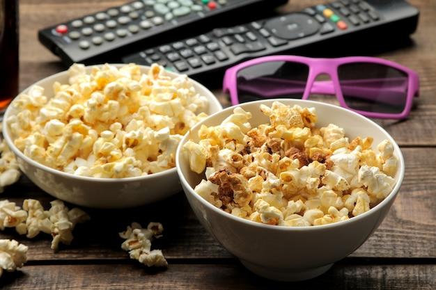 Popcorn, occhiali 3d e telecomando della tv su un tavolo in legno marrone, concetto di guardare film a casa.