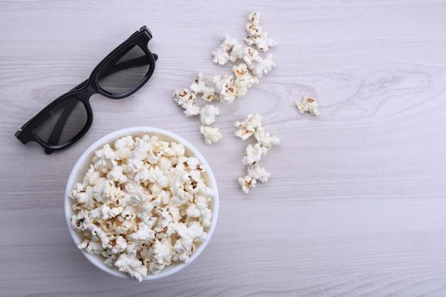 Popcorn in una ciotola e occhiali 3d su un legno chiaro