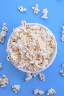 Popcorn in una ciotola su uno sfondo blu. avvicinamento. vista dall'alto