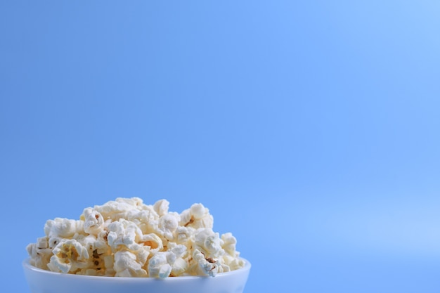 Popcorn in una ciotola su uno sfondo blu. avvicinamento. vista dall'alto.