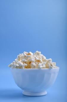 Popcorn in una ciotola su una parete blu. avvicinamento. vista dall'alto.