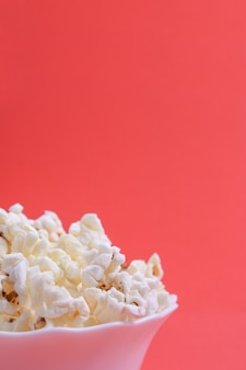 Popcorn in una ciotola su uno sfondo rosso. avvicinamento. vista frontale