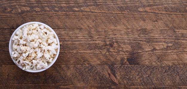 Popcorn in una ciotola su uno sfondo rosso. avvicinamento. vista dall'alto