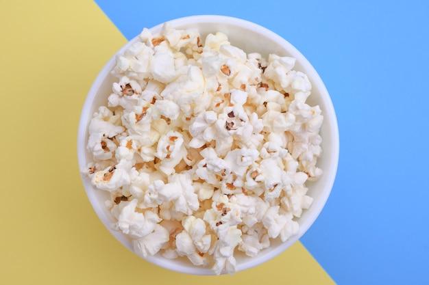 Popcorn in una ciotola su uno sfondo rosso. avvicinamento. vista dall'alto.
