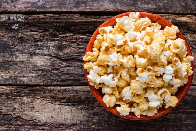 Popcorn in una ciotola su un fondo di legno