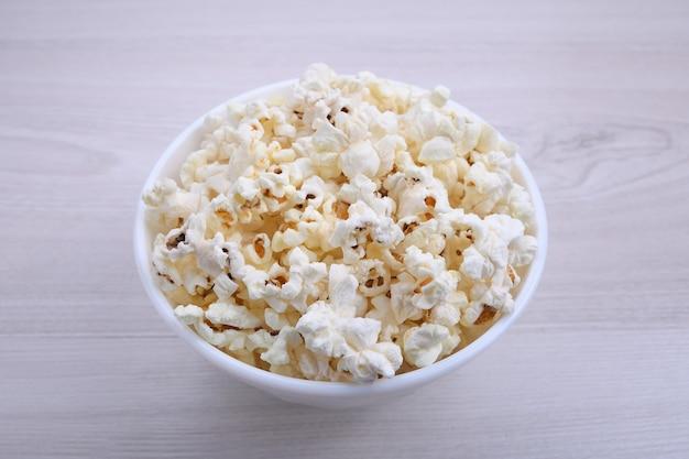 Popcorn in una ciotola su una superficie di legno. avvicinamento. vista dall'alto.