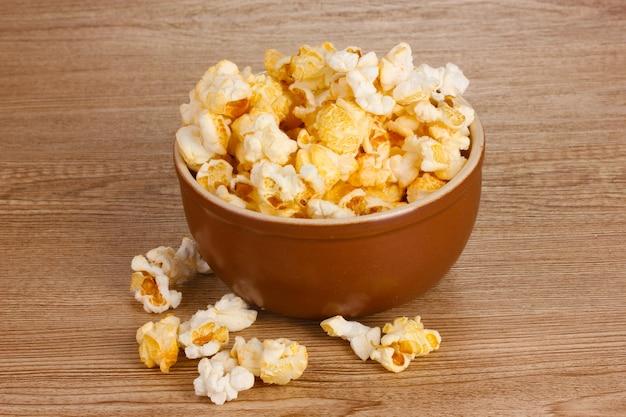 Popcorn in ciotola marrone sulla tavola di legno