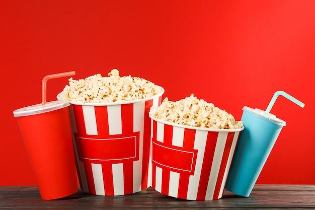 Secchi di popcorn e bicchieri di carta su sfondo rosso