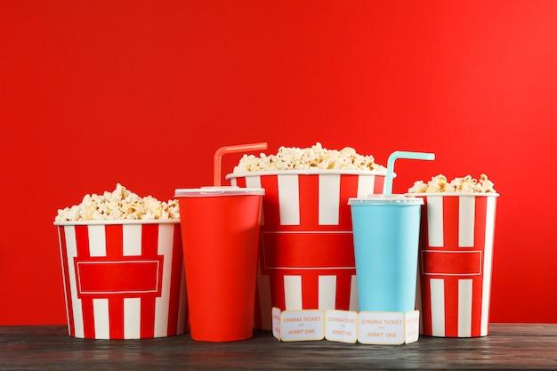 Secchi di popcorn, bicchieri di carta e biglietti su sfondo rosso