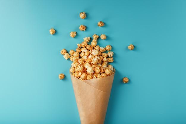 Popcorn in glassa al caramello in una busta di carta su sfondo blu. delizioso elogio per la visione di film, serie, cartoni animati. spazio libero, vista dall'alto. concetto minimalista.