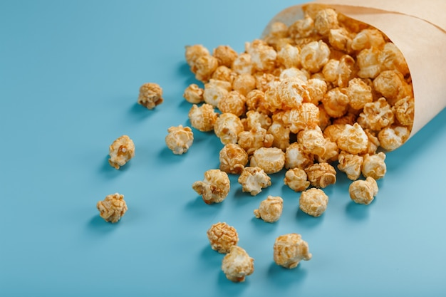 Popcorn in glassa al caramello in una busta di carta su un blu.
