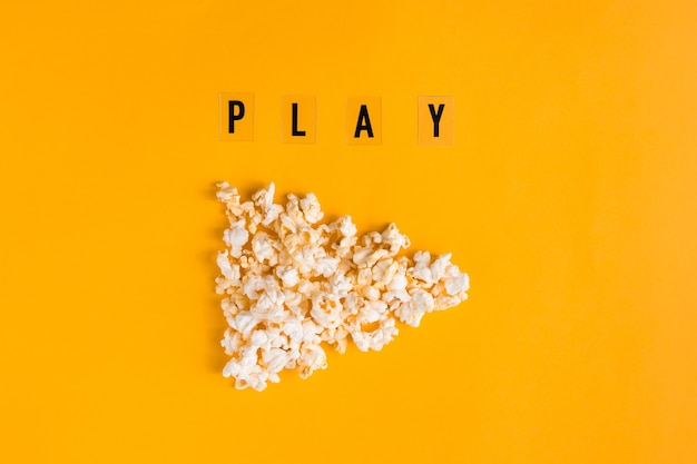 Popcorn a forma di pulsante di riproduzione e testo play su sfondo giallo. banner piatto, vista dall'alto. per andare al concetto di cinema. mi piace guardare i film.