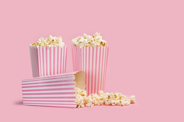 Popcorn in secchi a strisce su uno sfondo rosa Foto Premium