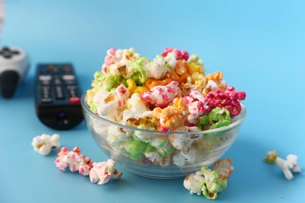 Popcorn e telecomando della tv sull'azzurro