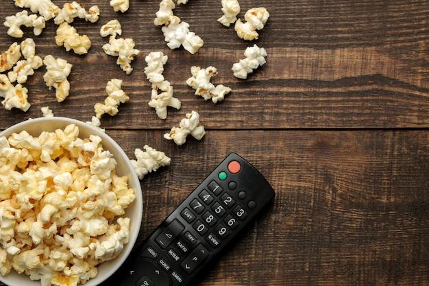 Popcorn e telecomando della tv su un fondo di legno marrone. concetto di guardare film a casa. vista dall'alto con spazio per il testo