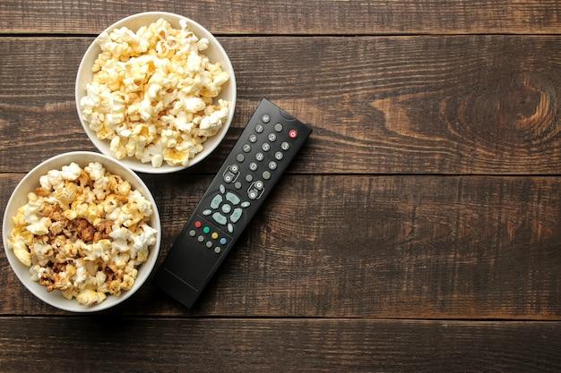 Popcorn e telecomando tv su un tavolo in legno marrone, concetto di guardare film a casa, vista dall'alto