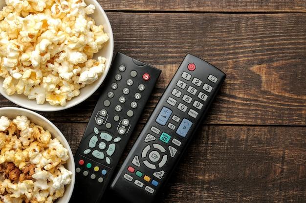 Popcorn e telecomando della tv su un tavolo in legno marrone, concetto di guardare film a casa, vista dall'alto