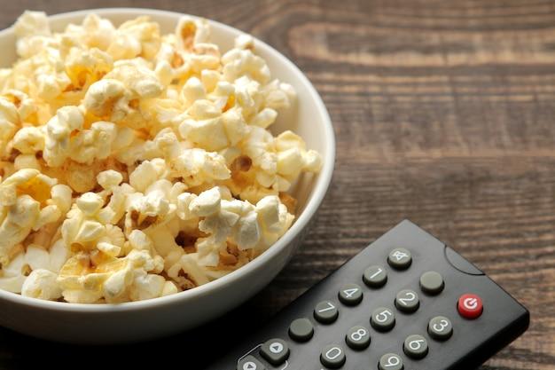 Popcorn e telecomando della tv su un tavolo in legno marrone, concetto di guardare film a casa.