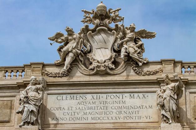 Emblema di papa clemente xii tra gli angeli con le trombe nella parte superiore della fontana di trevi a roma