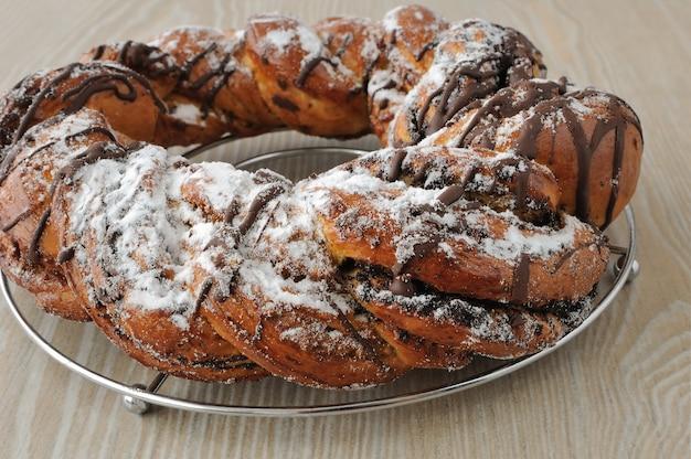 Rotolo di semi di papavero, guarnito con cioccolato e zucchero a velo