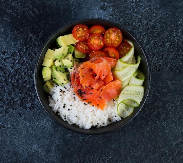 Un popolare piatto hawaiano, poke in un piatto di pesce rosso, riso e verdure. vista dall'alto.