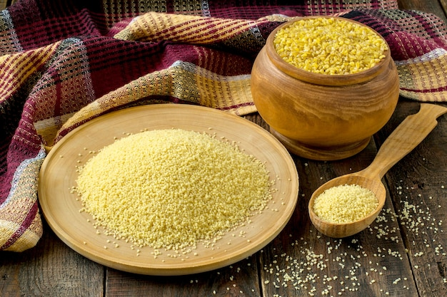Ingredienti popolari cucina orientale bulgur e couscous in piatto di legno e cucchiaio