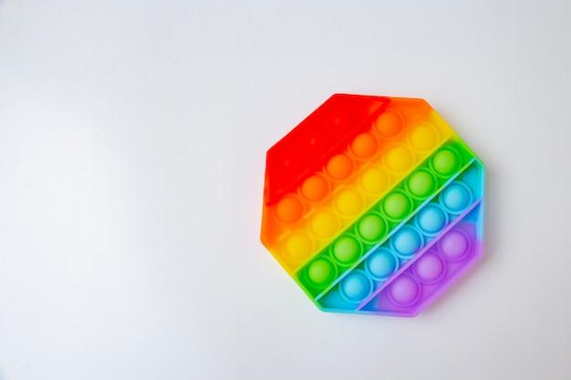 Popolare giocattolo antistress colorato in silicone pop it a forma di esagono su una superficie bianca.