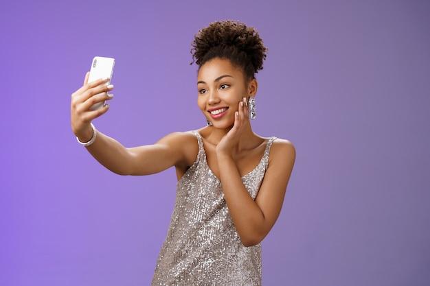 Popolare elegante blogger afro-americana femminile prendere selfie party night club estendere il braccio tenendo lo smartphone in posa guardando il display del telefono felicemente sorridendo in piedi sfondo blu in abito elegante.