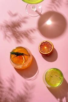 Cocktail alcolici ghiacciati estivi popolari serviti sotto la luce del sole estivo, vista dall'alto. stile retrò alla moda con le ombre.