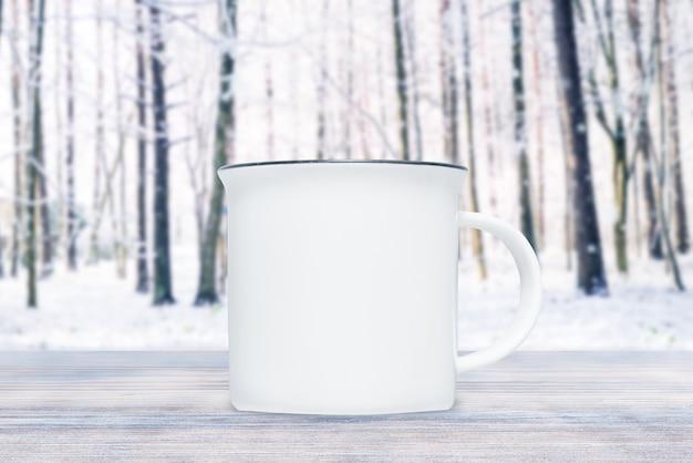 Tazza di porcellana in precipitazioni nevose nel giorno di inverno sulla tavola di legno