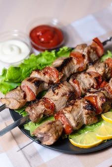 Barbecue di maiale con insalata e fette di limone su un piatto nero su spiedini con salsa