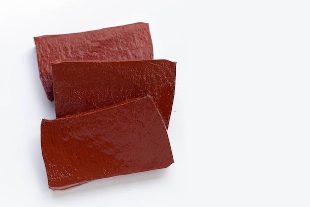 Budino di sangue di maiale nel piatto bianco su sfondo bianco.