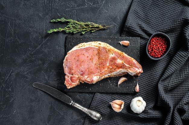 Maiale con osso. cotoletta per grigliare. con spezie e ingredienti aglio. carne biologica cruda sfondo nero. vista dall'alto