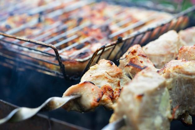 Lo shashlik di maiale e pollo viene grigliato sulla griglia all'aperto a casa in estate.