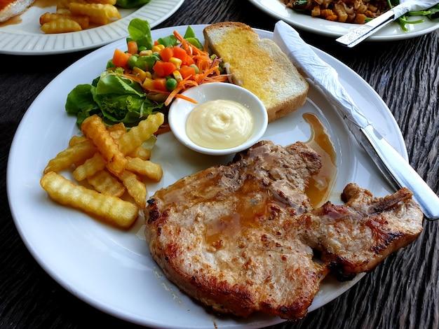 Bistecca di braciola di maiale con patatine fritte e insalata mista su un piatto bianco