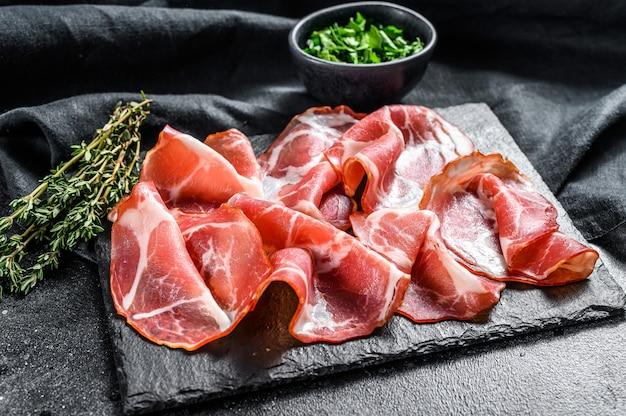 Prosciutto crudo del maiale vicino alle spezie