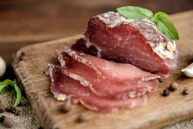 Fette di carne di maiale essiccate su fondo rustico in legno scuro. prosciutto di prosciutto di maiale essiccato alle erbe.