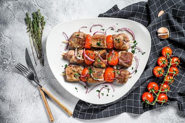 Spiedino di maiale su spiedini con pomodoro e pepe. cibo per un picnic. sfondo grigio. vista dall'alto.