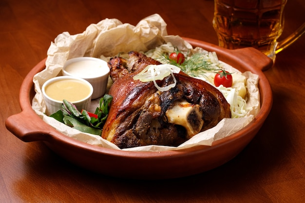 Stinco di maiale con senape e salsa bianca in un piatto di argilla e un bicchiere di birra leggera su un tavolo di legno. il concetto di pasti