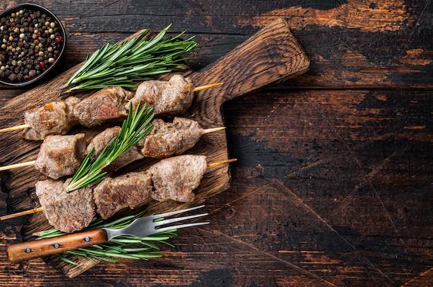 Carne di maiale shish kebab su spiedini con erbe su una tavola di legno