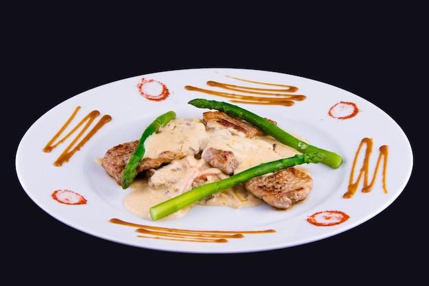 Medaglioni di maiale agli asparagi: filetto di maiale, asparagi, funghi, porri, cipolle, carote e salsa demi-glace.